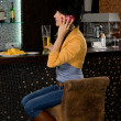 Stylish woman sitting at a bar counter — Stock Photo