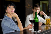 Sophisticated young woman drinking at a bar — Stock Photo