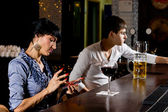 Stylish woman at the bar sending an sms message — Stock Photo