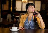 Young woman enjoying wine and coffee — Stock Photo