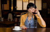Woman drinking wine and coffee at a bar counter — Stock Photo