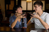 Young couple drinking red wine at a bar counter — Stock Photo