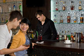 Young man chatting up a woman at the bar — Stock Photo