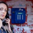 Woman making a public telephone call — Stock Photo