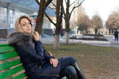 Woman sitting on a bench in an urban park — Stock Photo