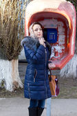 Pretty woman shopper at a public phone booth — Stock Photo