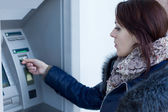 Woman retrieving her bank card at the ATM — Stock Photo