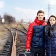 Young couple waiting on railway tracks — Stock Photo #38424479