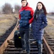 Stock Photo: Impatient young couple waiting on train tracks