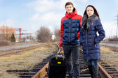 Young couple with a case waiting for the train — Stock Photo