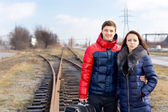 Young couple waiting on the railway tracks — Stock Photo