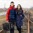 Постер, плакат: Young couple standing arm in arm with luggage