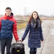 Stock Photo: Smiling young couple pulling along suitcase