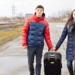Young man and woman pulling along a suitcase — Stok fotoğraf