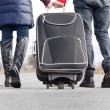 Stock Photo: Low angle view of couple pulling suitcase