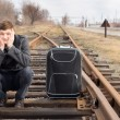 Bored young man waiting for a delayed train — Stock Photo