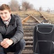 Young man waiting at a rural siding for a train — Stock Photo #38621145