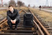 Young man waiting for a train at a siding — Stock Photo