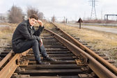 Young man sitting on the metal track of a railroad — Stock Photo