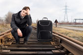 Bored young man waiting for the arrival of a train — Stock Photo