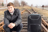 Young man waiting at a rural siding for a train — Stock Photo