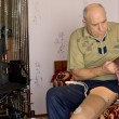 Senior man sitting on his bed fitting a prosthesis — Stock Photo #39974021