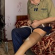Постер, плакат: Senior man attaching a prosthetic limb to his leg