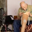 Stock Photo: Senior mchecking cup on his prosthetic leg