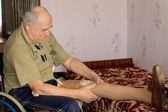 Elderly amputee fitting his artificial leg — Stock Photo