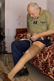 Senior man attaching a prosthetic limb to his leg — Stock Photo