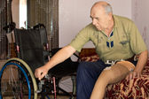 Senior man with an artificial leg and wheelchair — Stock Photo
