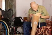 Senior man checking the cup on his prosthetic leg — Stock Photo