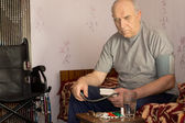 Senior handicapped man taking his blood pressure — Stock Photo