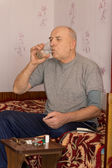Elderly amputee sitting taking his medication — Stock Photo