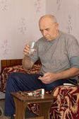 Unwell senior man taking medication — Stock Photo