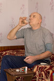 Senior man swallowing down his medication — Stock Photo