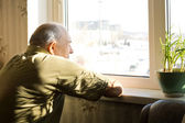 Lonely old man staring out of a window — Stock Photo