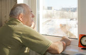 Senior man standing reminiscing at a window — Stock Photo