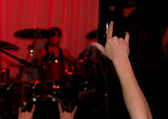 Audience at a rock concert giving the horns sign — Stock Photo