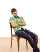 Handsome young man sitting slumped in a chair — Stock Photo