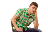 Watchful young man sitting thinking — Stockfoto