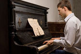 Young man practising at a piano — Stock Photo
