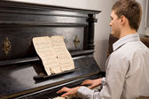 Young man playing music on a wooden piano — Stock Photo