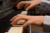 Male pianist playing music on an ivory keyboard — Stock Photo