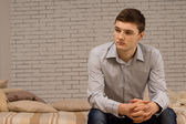 Young man sitting on a sofa thinking — Stock Photo