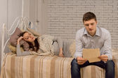 Man sitting reading watched by his girlfriend — Stock Photo