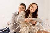 Smiling beautiful couple on a wrought iron bed — Stock Photo