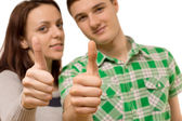 Attractive young couple giving a thumbs up — Stock Photo
