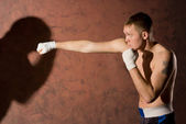 Young boxer punching his opponent — Stock Photo