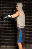 Young boxer working out against a brick wall — Stock Photo